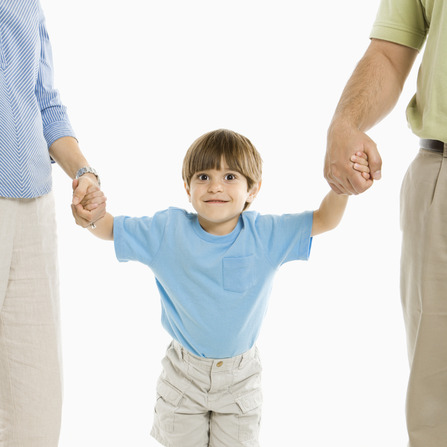 Boy holding hands with parents standing against white background.