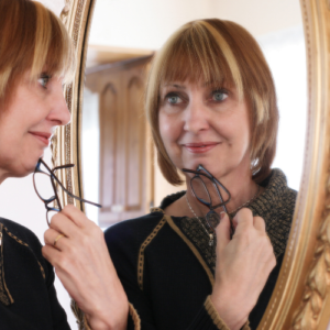 Woman looking in mirror at herself.
