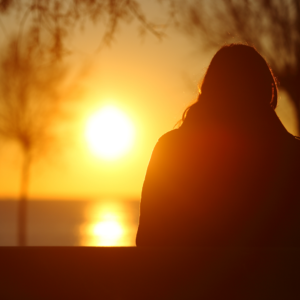 Person sitting and watching the sunset.