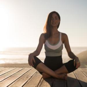 Woman sitting cross legged in yoga pose.